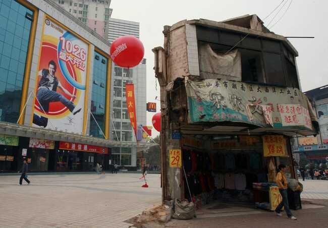 Ngôi nhà cuối cùng trong khu vực này nằm trước một trung tâm mua sắm ở trung tâm tỉnh Hồ Nam của Trung Quốc.