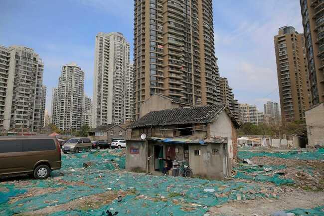 """Cư dân của khu vực Guangfuli của Thượng Hải đã quyết định không rời khỏi nhà của họ, tạo ra cả một """"khu phố đinh"""". Tao Weiren ngồi trước ngôi nhà hai tầng của mình ở đó, hiện được bao quanh bởi các tòa nhà chung cư cao cấp."""