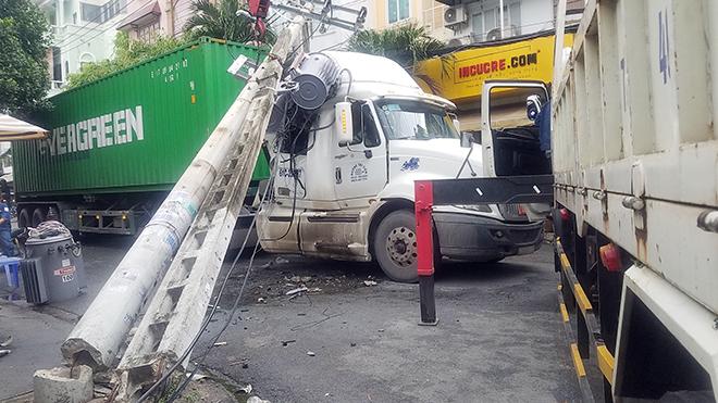 Vướng dây cáp, xe container kéo gãy 2 cột điện ở Sài Gòn - 1