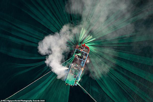 Nhiếp ảnh gia Việt Nam Thiên Nguyễn được vinh danh là Nhiếp ảnh gia trên không của năm 2020 ở hạng mục Con người với bức ảnh khói bốc ra từ động cơ của một chiếc thuyền đánh bắt cá cơm trên bờ biển Phú Yên.